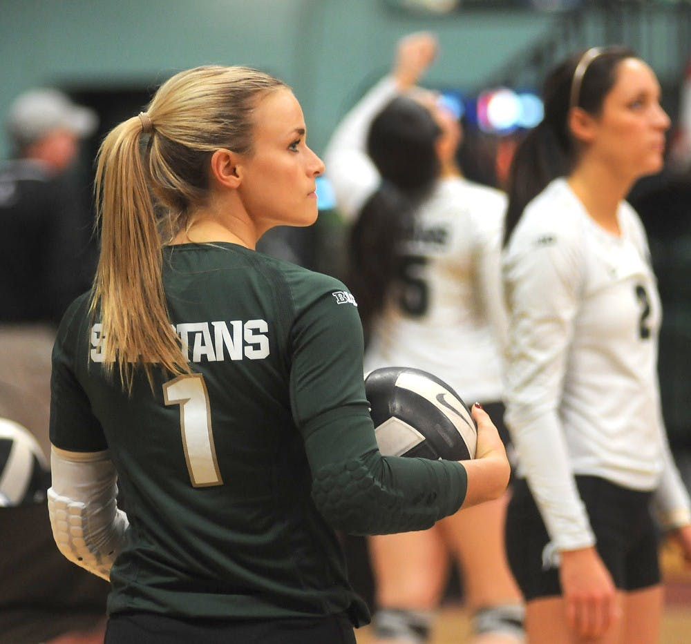 <p>Senior libero Kori Moster warms up Nov. 22, 2014 before the game against Rutgers at Jenison Field House. The Spartans defeated the Scarlet Knights, 3-0. Dylan Vowell/The State News</p>