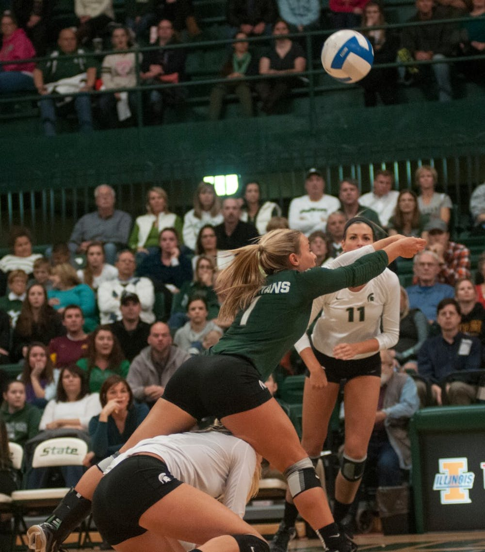 <p>Senior libero Kori Moster digs the ball as she steps over freshman setter Rachel Minarick during the game against Minnesota on Nov. 7, 2014 at Jenison Field House. The Gophers defeated the Spartans, 3-1. Aerika Williams/The State News</p>