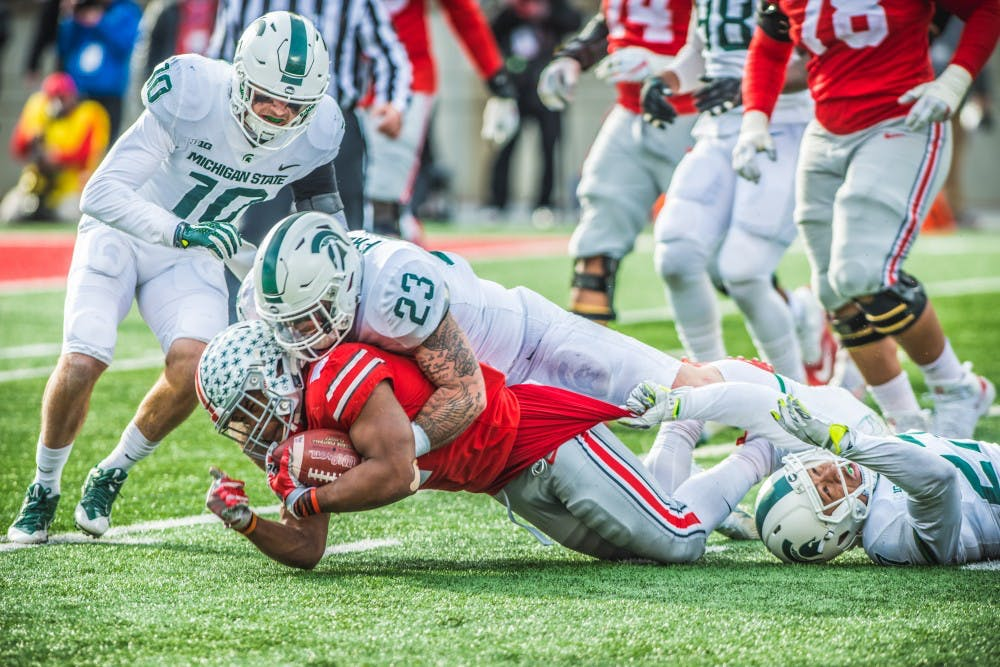 <p>Ohio State running back J.K. Dobbins (2) is tackled by senior linebacker Chris Frey (23) during the game against Ohio State, on Nov. 11, 2017, at Ohio Stadium. The Spartans were defeated by the Buckeyes, 48-3.</p>