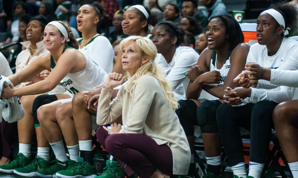 Head Coach Suzy Merchant and the rest of the team watch from the sidelines as a player shoots the ball during the game against Oakland on Nov. 13, 2017, at Breslin Center. The Spartans defeated the Grizzlies 95-63.