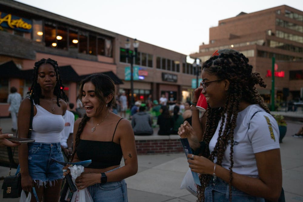 <p>Sophomore Claire Duris (center) during an interview at Moonlight Extrava - GRAND- za on Monday, Aug. 30, 2021 that went from 8 p.m. to 12 a.m. (EDT) and streched down Albert Avenue in downtown East Lansing. </p>