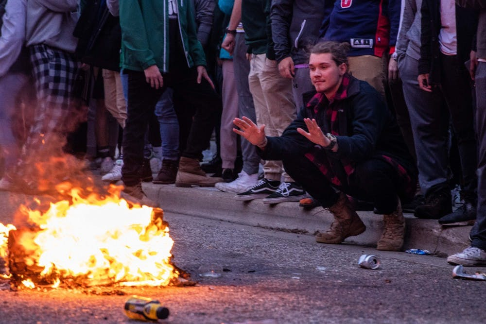 A fan warms his hands over a burning couch as police move people away after MSU's victory over Duke in the Elite Eight in Cedar Village Apartments March 31, 2019.