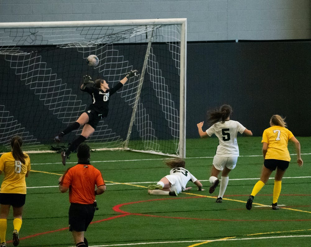 <p>University of Michigan&#x27;s Meredith Haakenson (7) scores a goal against the Spartans on March 12, 2021.</p>