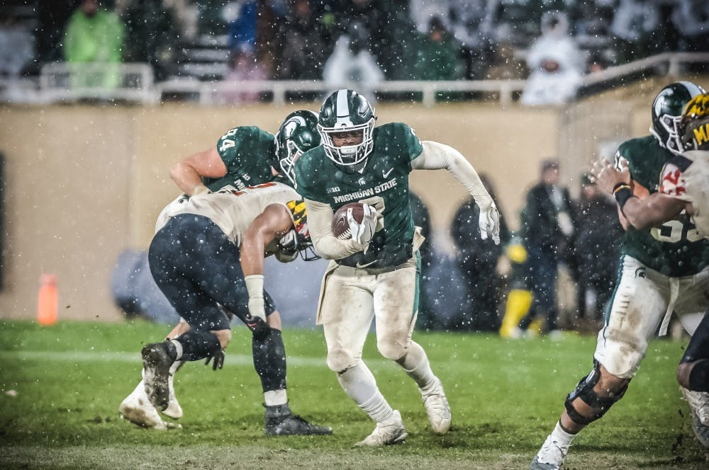 Junior running back LJ Scott (3) shoots through a gap during the game against Maryland on Nov. 18, 2017, at Spartan Stadium. The Spartans defeated the Terrapins, 17-7.