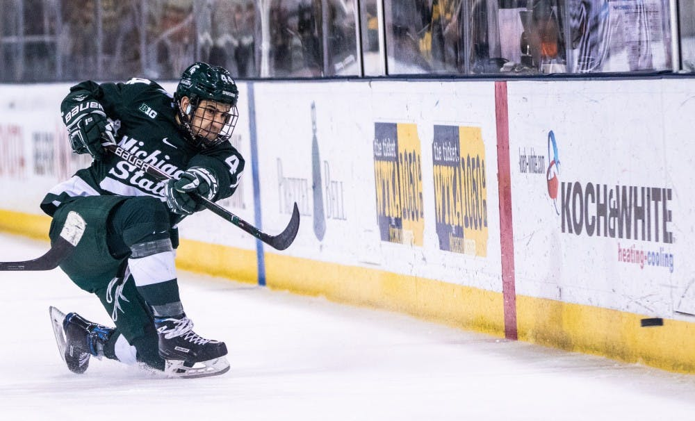 <p>Junior defenseman Butrus Ghafari (44) passes the puck up the boards during the game against Michigan on Feb. 8, 2019, at Yost Ice Arena. The Spartans fell to the Wolverines, 5-3.</p>