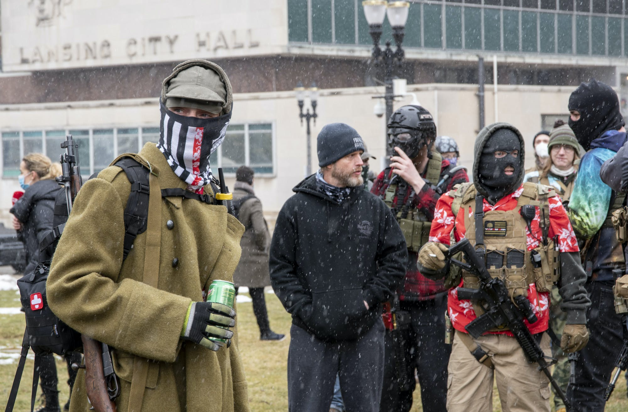 A group of people, some of them armed, some of them wearing ski masks, stand in front of a building that reads, 'Lansing City Hall.'