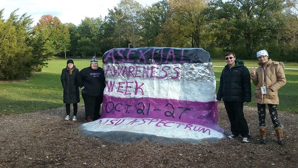 <p>Members of MSU A-Spectrum pose with the Rock after it was painted for Asexual Awareness Week 2018. <strong>Photo courtesy of MSU A-Spectrum.</strong></p>