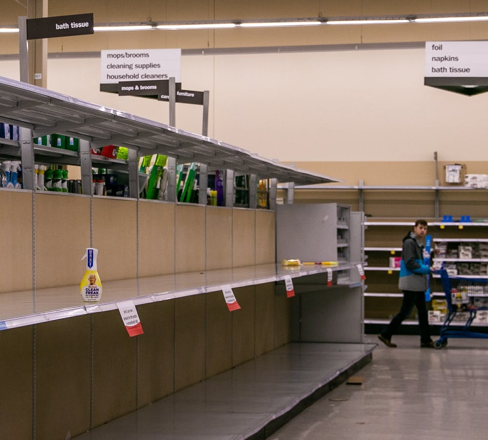 A man looks at the empty toilet paper shelves at Meijer March 12, 2020 after MSU cancelled classes due to coronavirus.