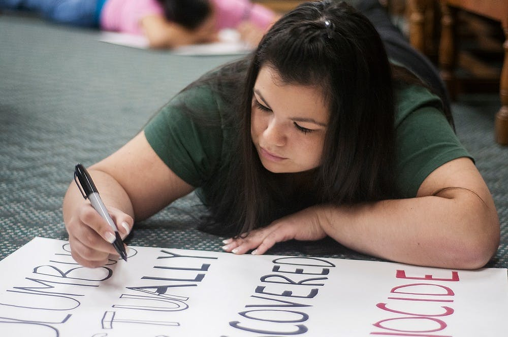 """<p>Lansing resident Bleu Bird draws a Columbus Day protest sign during a North American Indigenous Student Organization meeting Sunday, Oct. 7, in Hubbard Hall. <span class=""""caps"""">NAISO</span> is raising awareness for Indigenous People&#8217;s day across campus on Monday. Adam Toolin/The State News</p>"""