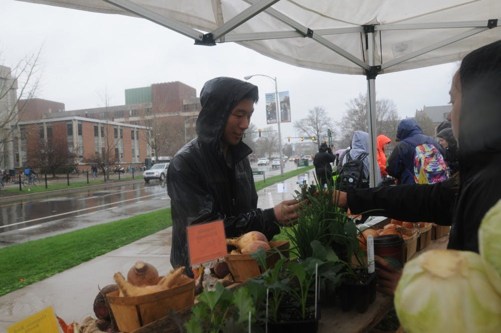 Media and information sophomore Jason Wu purchases vegetables on April 21, 2016 at the organic farm in front of MSU Auditorium.