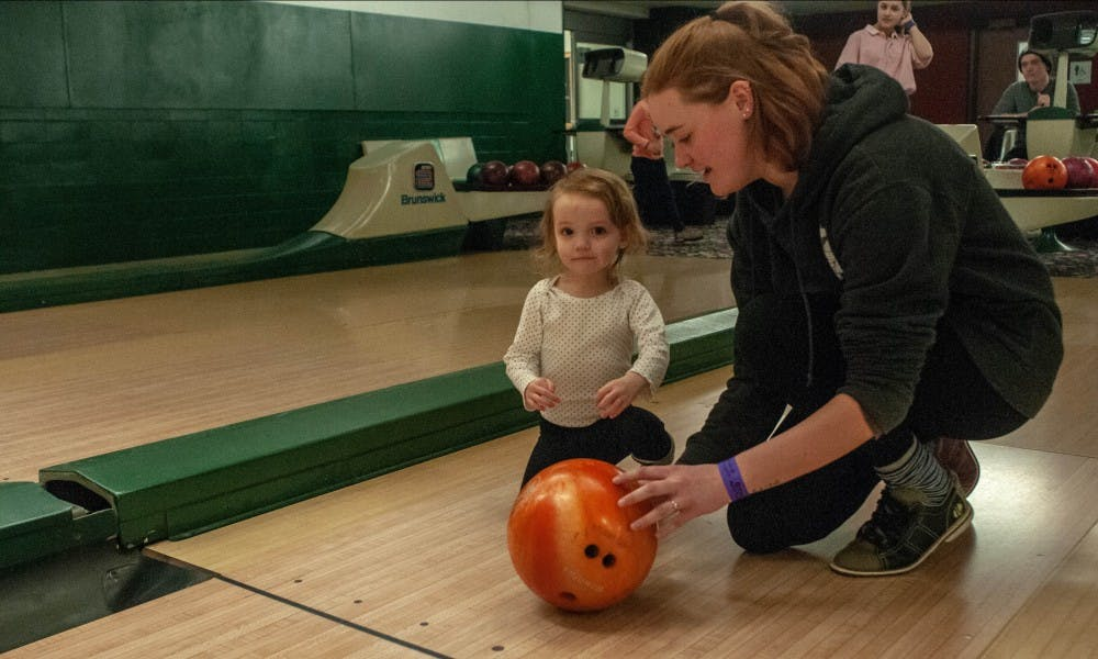 <p>Computer science junior Emma Taylor, right, helps Ruby Taylor, 2, left, bowl at the Sibs and Kids event at the MSU Union on Feb. 8, 2019.</p>