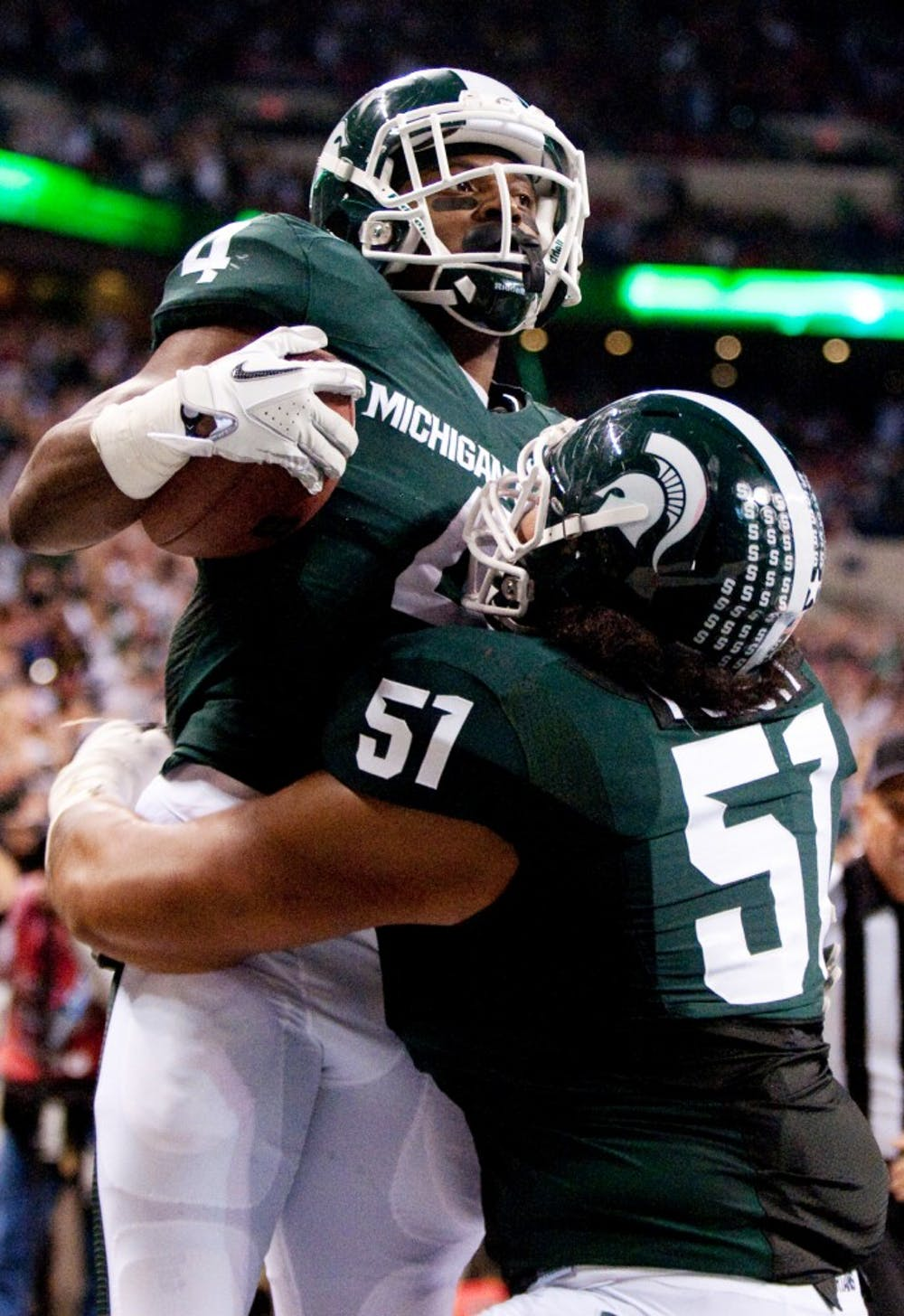 Junior offensive tackle Fou Fonti celebrates with junior running back Edwin Baker after he scored a toucdown. The Spartans lost to the Wisconsin Badgers, 42-39, in the Big Ten Championship game on Saturday night at Lucas Oil Stadium in Indianapolis, Ind. Josh Radtke/The State News