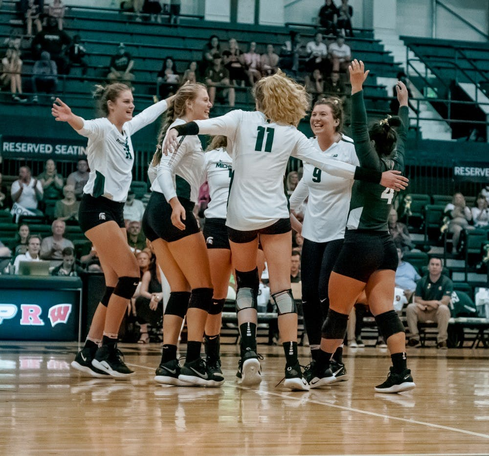 The Spartans celebrate with each other after a point during the game against Albany on Sept. 14, 2018 at Jenison Fieldhouse. The Spartans defeated the Great Danes, 3-0.