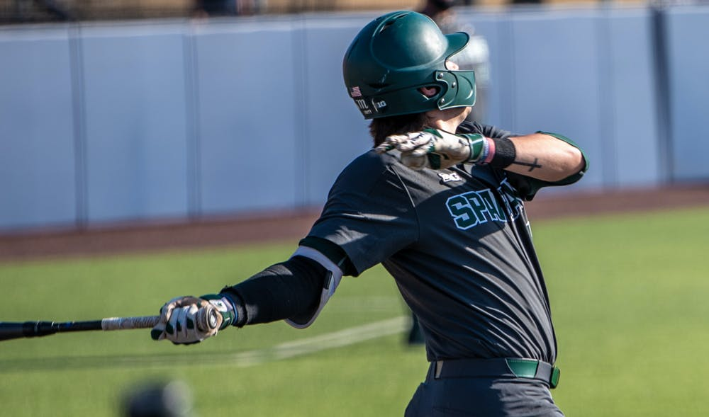 <p>Freshman infielder Brock Vradenburg (48) hits the ball resulting in a single. The Wolverines made a comeback in the ninth inning to top the Spartans, 8-7, at Ray Fisher Stadium on March 21, 2021.</p>