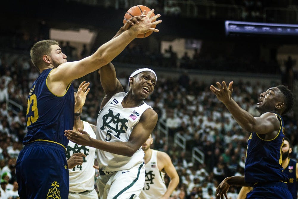 Sophomore guard Cassius Winston (5) goes in for a basket as Notre Dame forward Geben Martinas (23) attempts to block during the game against Notre Dame on Nov. 30, 2017 at Breslin Center. The Spartans took down the Fighting Irish, 81-63.