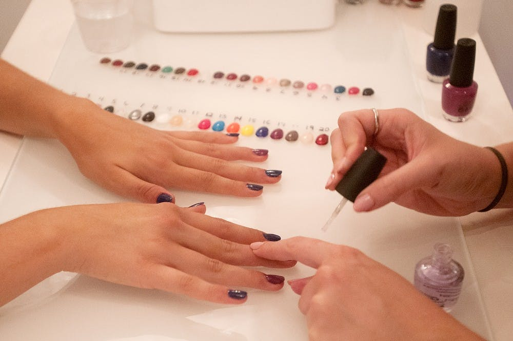 <p>Journalism junior Hannah Watts, left, gets her nails painted by Okemos, Mich., resident Morgane Dalton on Sept. 10, 2014, at Heat Blow Dry and Beauty Boutique, 2900 Hannah Blvd. Jessalyn Tamez/The State News</p>
