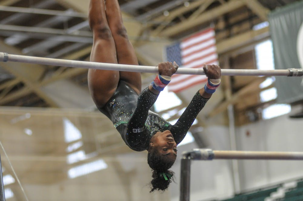 <p>Roya Shirley on the bars at the women's gymnastics meet at Jenison Field House March 17, 2019. The Spartans placed first against Alaska, Ball State and UIC.</p>