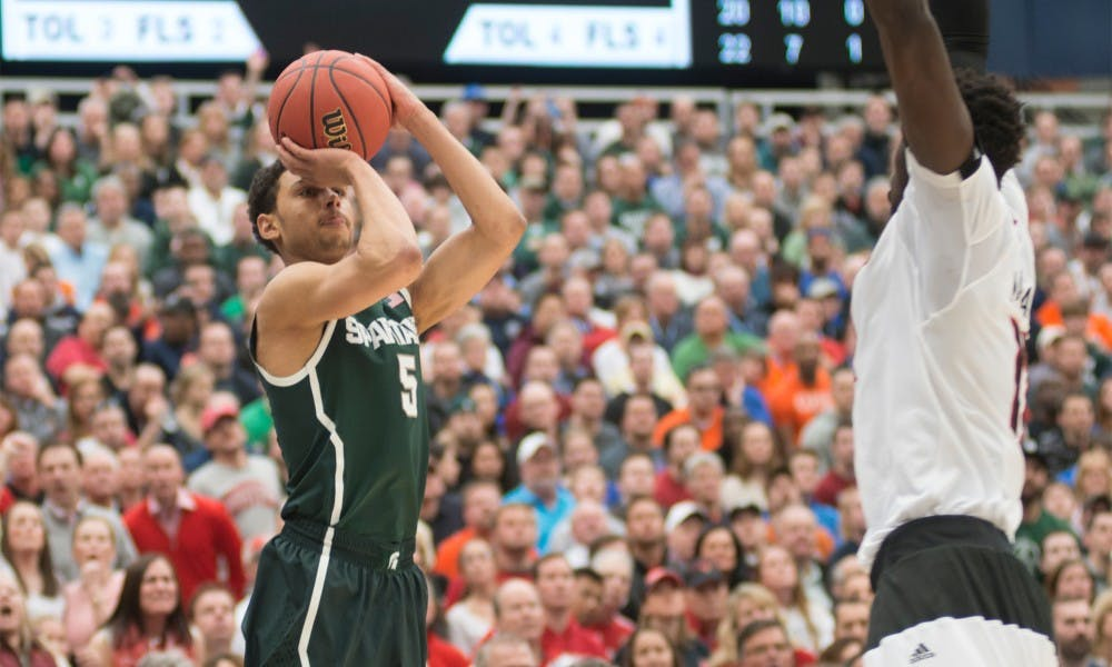 Junior guard Bryn Forbes attempts a basket March 29, 2015, during the East Regional round of the NCAA Tournament in the Elite Eight against Louisville at the Carrier Dome in Syracuse, New York. The Spartans defeated the Cardinals in overtime, 76-70. Erin Hampton/The State News