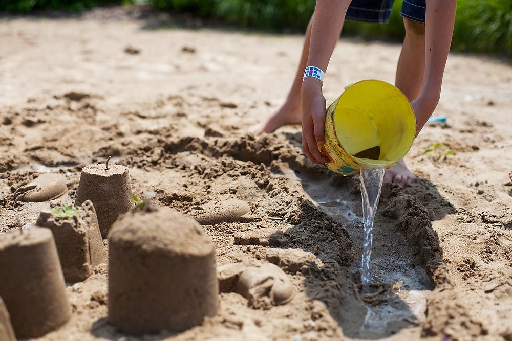 <p>East Lansing resident Alexander Stacey builds sand castles during the 2014 Summer Splash event, July 30, 2014, at the East Lansing Family Aquatic Center. Activities at the event included a sand castle building contest, a belly flop contest and a balloon toss. Corey Damocles/The State News</p>