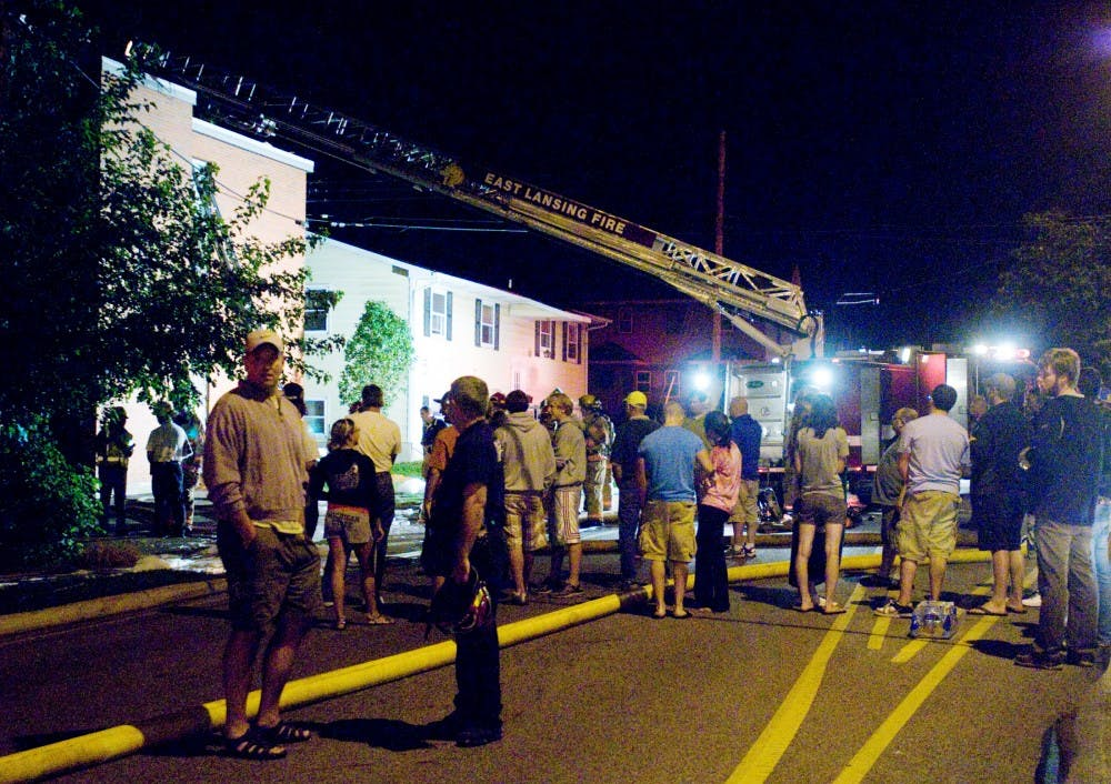 <p>Residents and neighbors linger in the street after a fire erupted at 129 Burcham Apartments late Monday night. Leo Allaire, not pictured, was one of 12 East Lansing firefighters dispatched to the fire, which spread through the walls of the apartment complex and damaged three units. All residents were evacuated and unharmed.</p>
