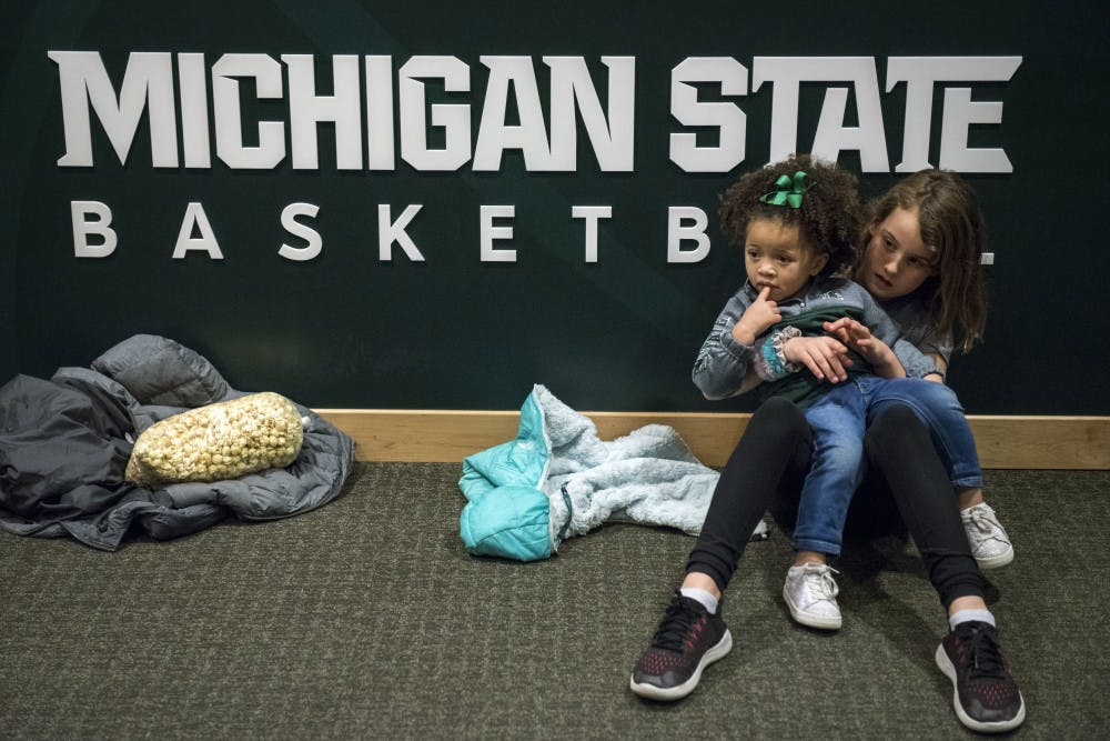 Ayanna Tillman, 2, waits with Quinn Fife, 9, of East Lansing, for her father, sophomore forward Xavier Tillman (23), to come out of the locker room after the men's basketball game against Ohio State at Breslin Center on Feb. 17, 2019. The Spartans defeated the Buckeyes, 62-44. Nic Antaya/The State News