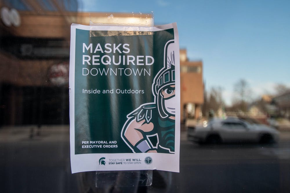 A sign posted on a window in downtown East Lansing on Nov. 20, 2020.