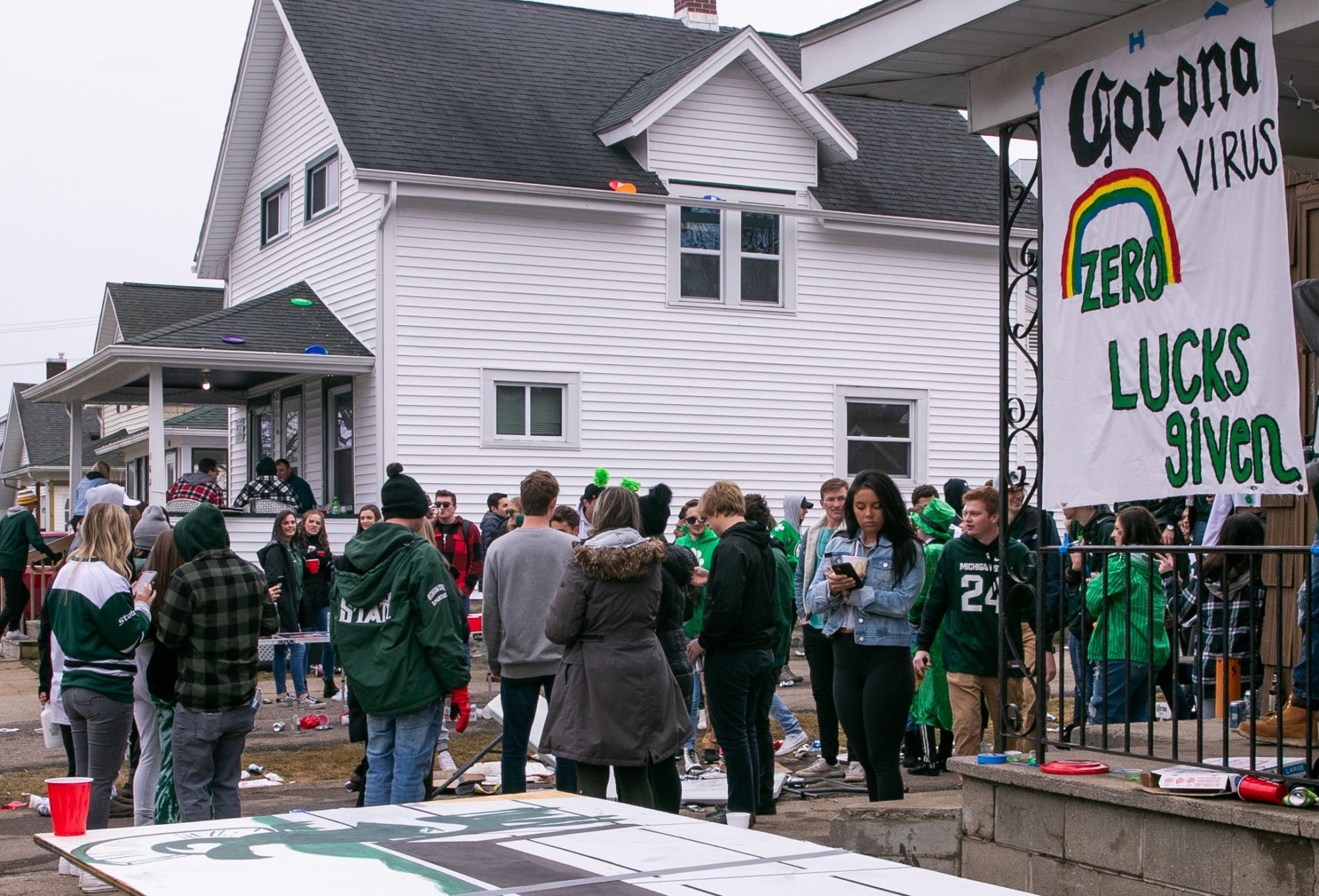 A large group of students, most wearing green clothing, gather in a yard in front of a two-story house. A sign hangs from a house in the foreground that reads, 'Corona virus zero lucks given.'