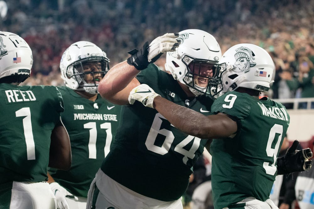 <p>Spartans share a quick celebration after junior running back Kenneth Walker lll (9) makes a touchdown during the homecoming game against Western Kentucky on Oct. 2, 2021. </p>