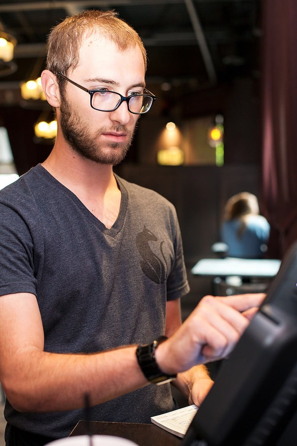 <p>Alumnus and East Lansing resident Seth Zundel serves food July, 30, 2014, at Black Cat Bistro in East Lansing. Zundel graduated with a degree in english in May, 2013 and is currently a server at Black Cat Bistro. Corey Damocles/The State News</p>