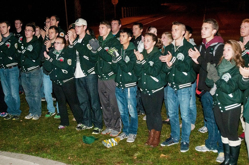 <p>The MSU Marching Band sings the fight song on Oct. 22, 2014, at the Spartan Statue. The band came out to show support for Sparty Watch. Raymond Williams/The State News</p>