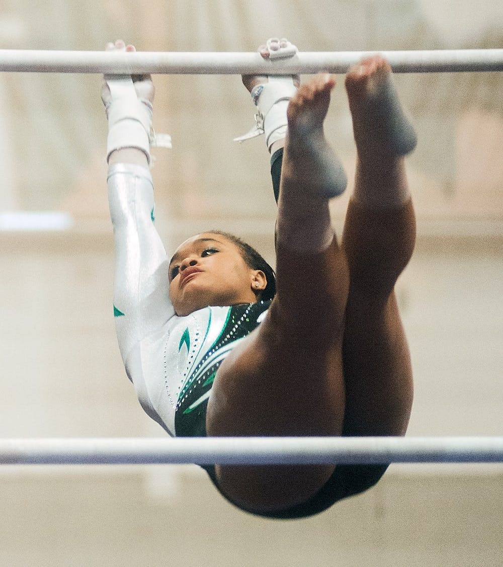 Sophomore gymnast Alina Cartwright competes in the uneven bars event during the meet against U-M on March 2, 2013, at Jenison Field House. MSU fell to U-M 197.3-194.875. Danyelle Morrow/The State News