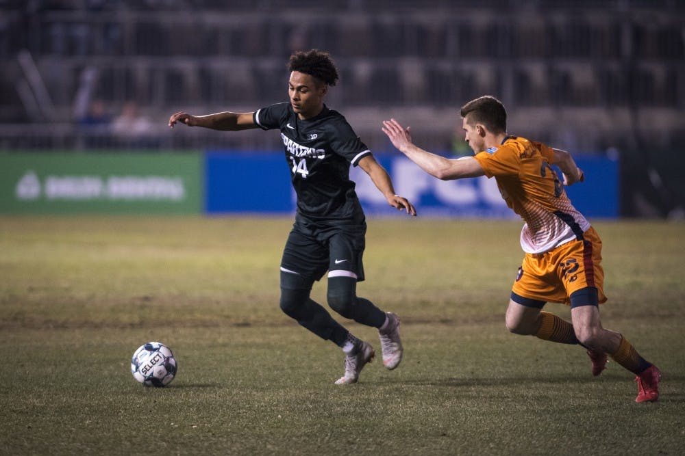 <p>Freshman defender Olu Ogunwale (14) handles the ball during the second half of the Capital Cup against Lansing Ignite FC at Cooley Law School Stadium in Lansing on Tuesday, April 16, 2019. Michigan State was defeated by Lansing Ignite, 4-0. </p>