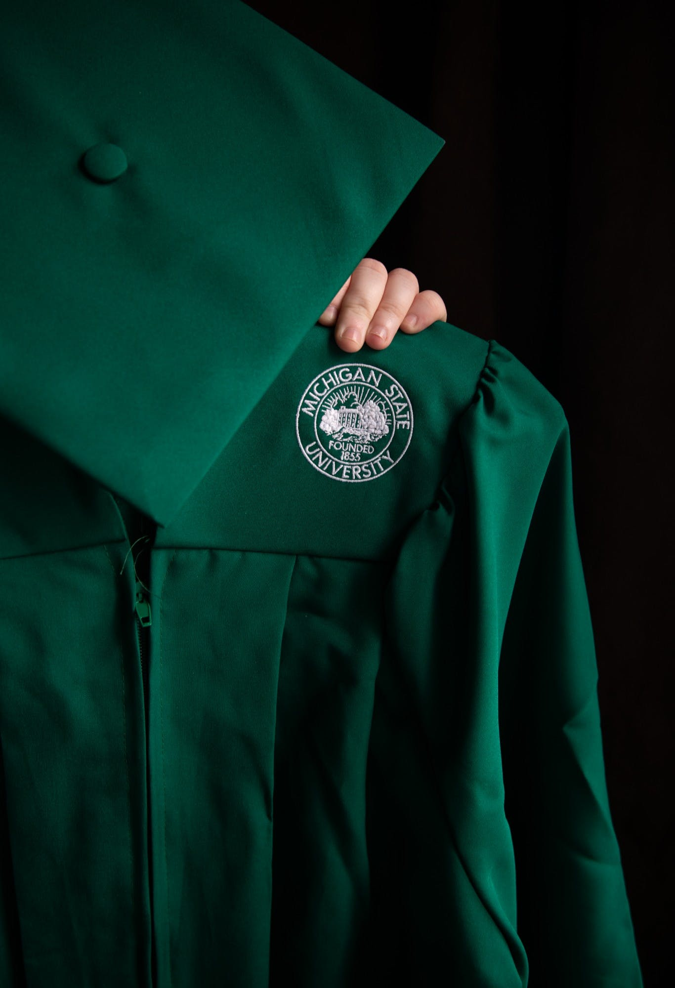 An image of a cap and gown againt a black background.
