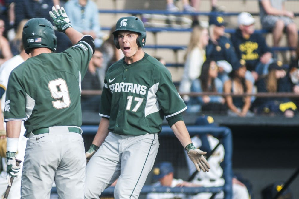 <p>Bryce Kelley (17), right, looks to low-five senior infielder Dan Durkin (9), left, after he scored a run against the University of Michigan on April 18, 2017 at Ray Fisher Stadium in Ann Arbor. The Wolverines defeated the Spartans, 12-4. Kelley is one of five seniors who returned to play in the 2021 season.&nbsp;</p>