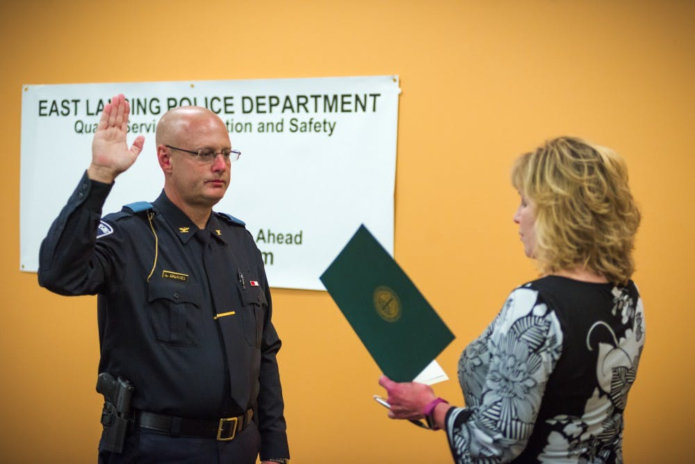 Interim Police Chief Larry Sparkes takes the oath of honor while being sworn in as East Lansing's chief of police on Aug. 25, 2017, at East Lansing Library. Sparkes has been appointed to the position in succession to Jeff Murphy. Murphy retired to take a position as the Director of Security for MSU's College of Human Medicine research facility.