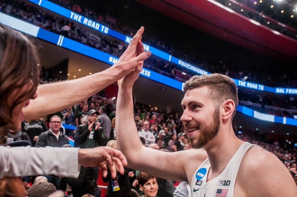 <p>Senior forward Ben Carter (13) high fives fans after the game against Bucknell on March 16, 2018 at Little Caesars Arena in Detroit. The Spartans defeated the Bison 82-78.</p>