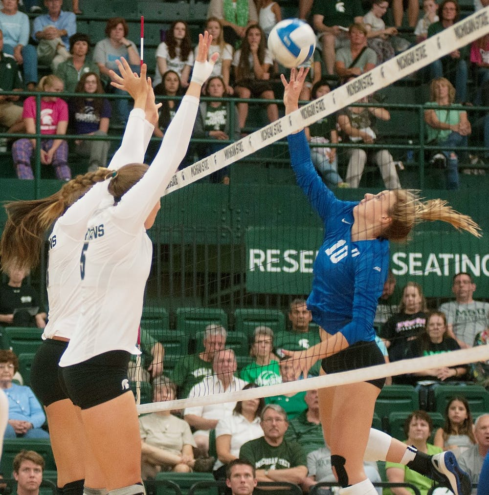 <p>Freshman outside hitter Holly Toliver and redshirt freshman middle blocker Megan Tompkins attempt to block Duke middle blocker Anna Kropf on Sept. 6, 2014 at Jenison Fieldhouse during a game against Duke University. The Blue Devils defeated the Spartans, 3-2. Aerika Williams/The State News </p>