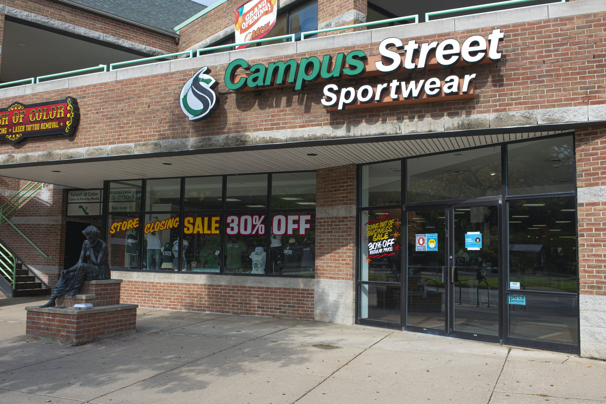 A brick building is pictured with window signs that read, 'store closing,' 'sale 30% off,' 'Going out of business sale 30% off at regular price.' Above the doorway to the building is a large sign that reads 'Campus Street Sportswear.'
