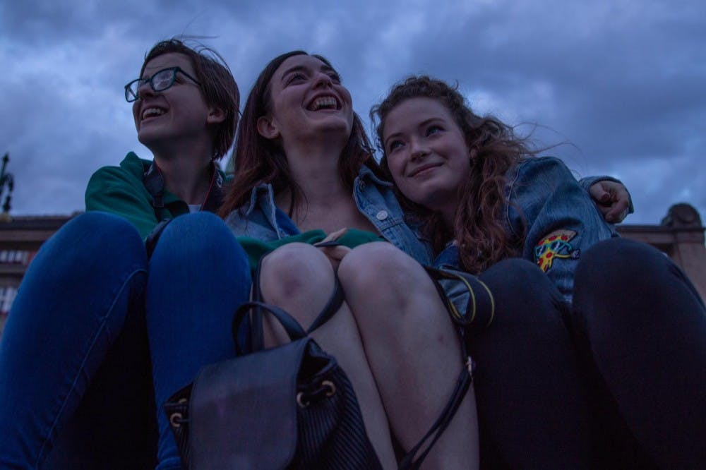 <p>Annie Barker (left), Haley Sinclair (middle) and Alyte Katilius (right) sit together in Prague on their photo communication in Europe study abroad.</p>