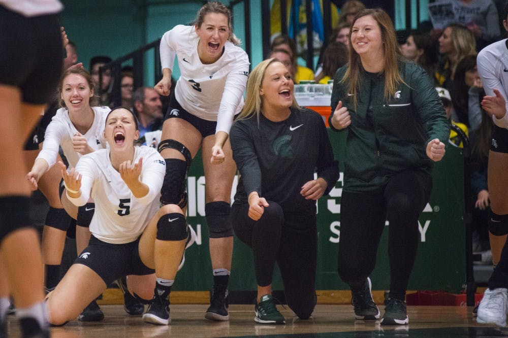 The team celebrates from the sidelines after scoring a point during the game against Michigan on Nov. 12, 2016 at Jenison Fieldhouse. The Spartans defeated the Wolverines, 3-1.