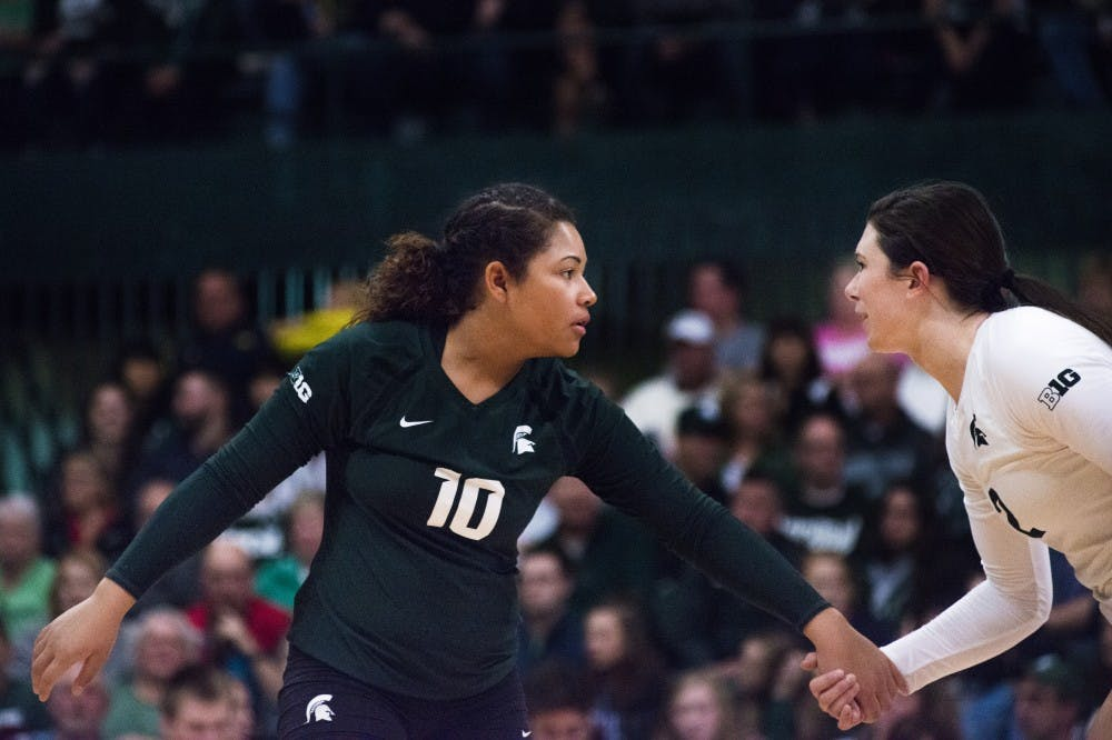 Junior defensive specialist Abby Monson (10) talks with junior outside hitter Autumn Bailey (2) before a play during the game against Michigan on Nov. 12, 2016 at Jenison Fieldhouse. The Spartans defeated the Wolverines, 3-1.