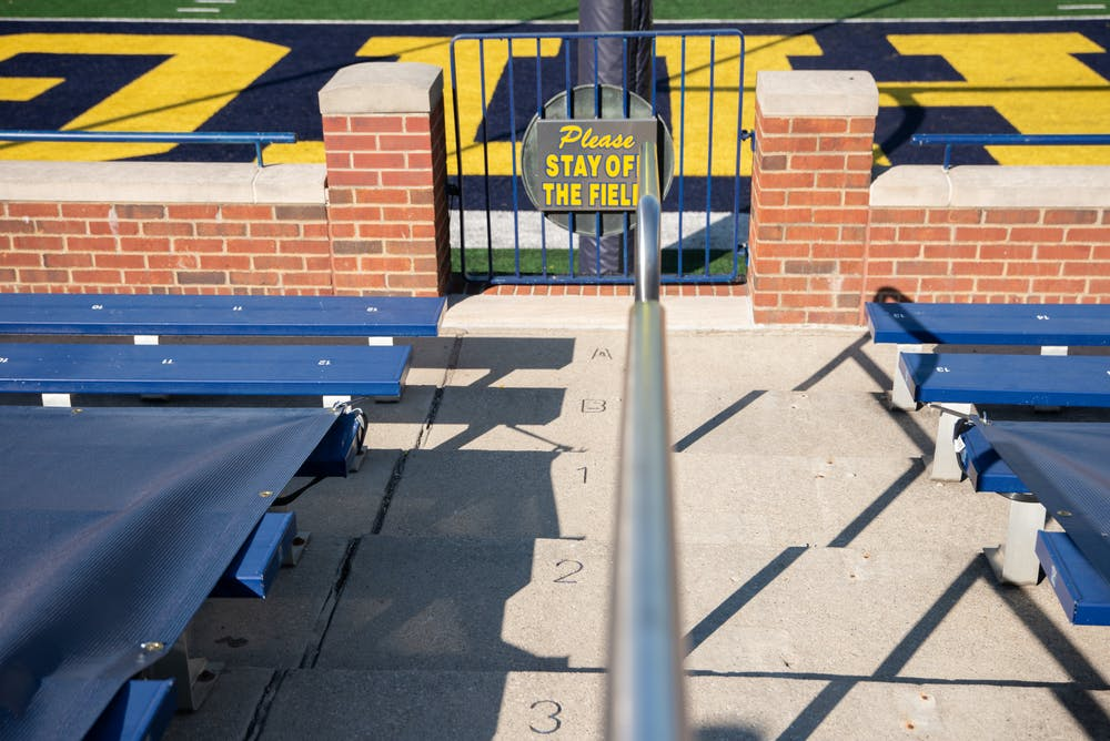 <p>A sign reads &quot;Please Stay Off The Field&quot; in a nearly empty big house on Oct. 31, 2020.</p>