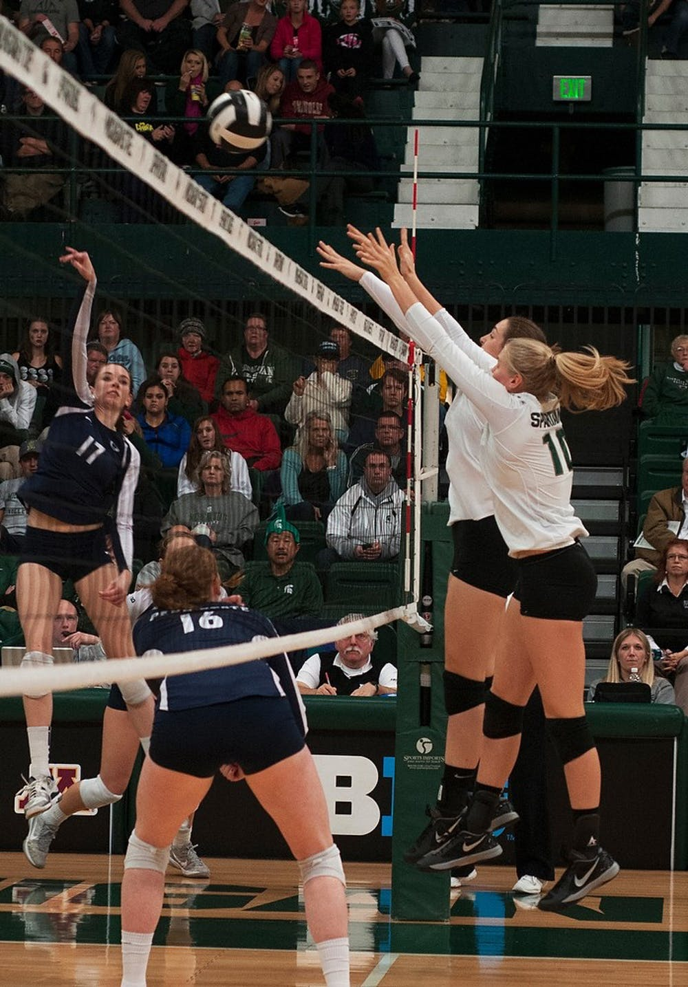 """<p>Senior middle blocker Kelsey Kuipers, left, and freshman middle blocker Allyssah Fitterer, right, block the ball Nov. 2, 2013, at Jenison Field House. <span class=""""caps"""">MSU</span> lost to Penn State, 3-0. Margaux Forster/The State News</p>"""