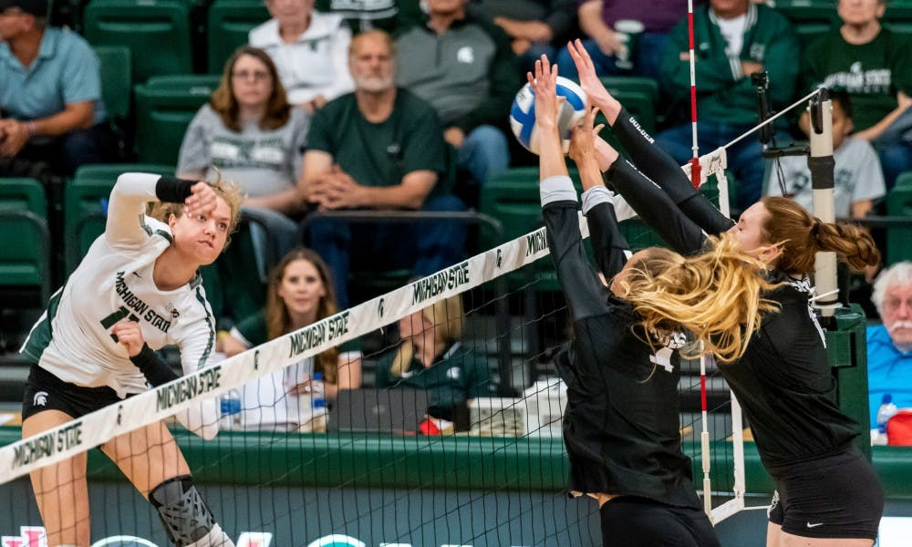 <p>Junior outside hitter Alyssa Chronowski (11) has her spike blocked against Oakland. The Spartans defeated the Golden Grizzlies, 3-0, at Jenison Field House on Sept. 12, 2019.</p>