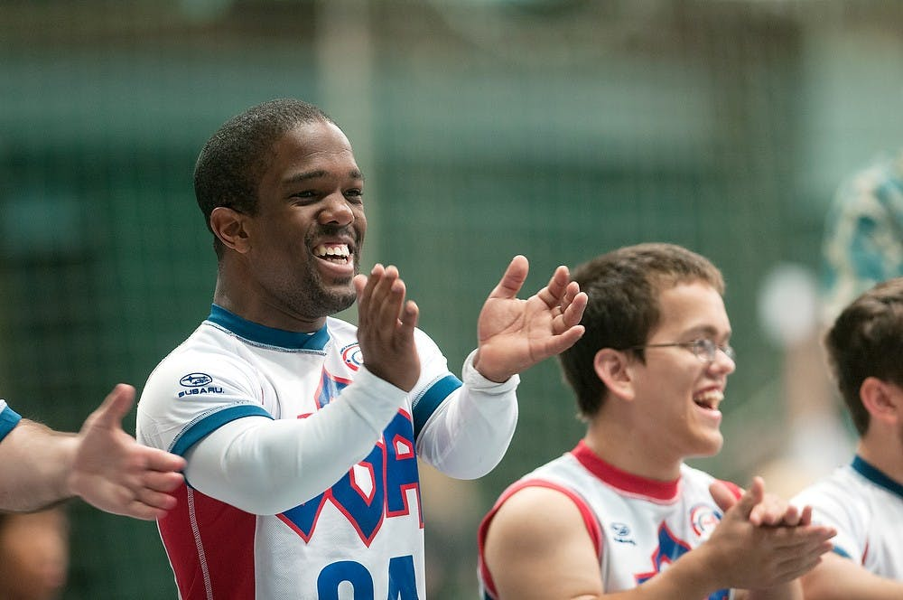 <p>Pittsburgh, Penn. resident Blaze Foster applauds his teammates after a point is scored, during a volleyball set of the 2013 World Dwarf Games, Aug. 8, 2013, at Jenison Field House. Foster, along with his teammates, went on to win a gold medal. Danyelle Morrow/The State News</p>