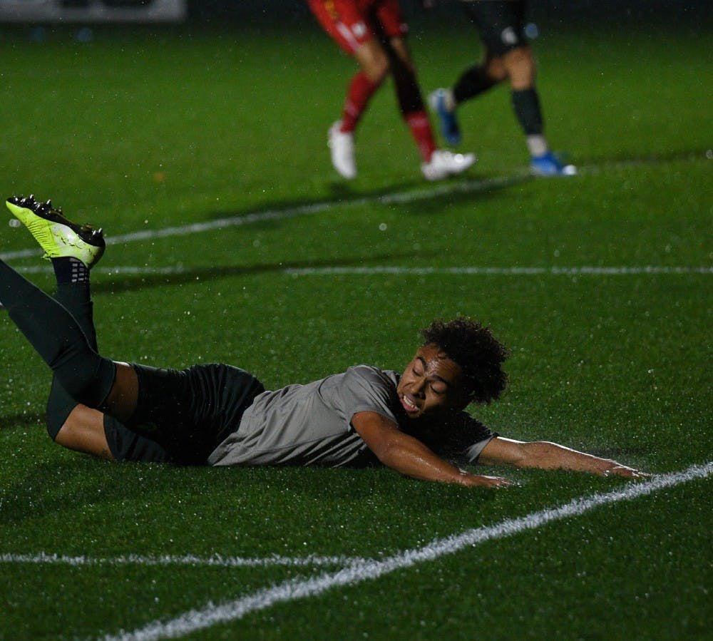 <p>Sophomore defender Olu Ogunwale (14) slides during the game against Maryland at DeMartin Stadium on October 11, 2019. The Spartans tied the Terrapins 1-1.</p>