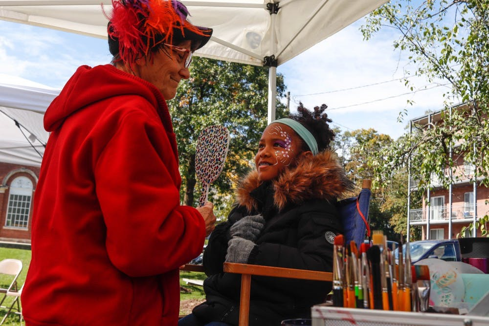 <p>Karen Miller, left, paints Madeline Huddleston's face, right, at Autumn Fest at the East Lansing Farmer&#x27;s Market on Oct. 13, 2019.</p>