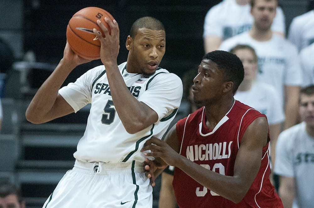 <p>Junior center Adreian Payne fends off Nicholls State forward JaMarkus Horace on Saturday, Dec. 1, 2012, during the game at Breslin Center. The Spartans defeated the Colonels 84-39. Julia Nagy/The State News</p>
