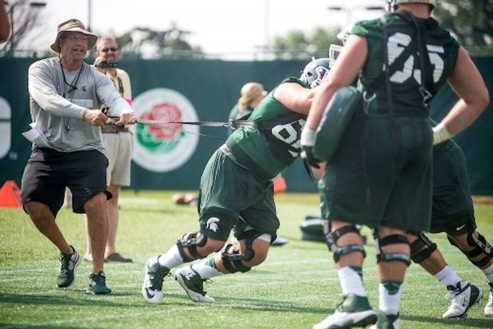 Offensive line coach Mark Staten runs practice drills Aug. 2, 2014, at the practice field outside Duffy Daugherty Football Building. Danyelle Morrow/The State News
