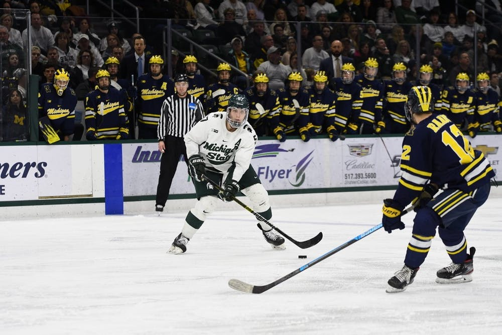 Redshirt senior defenseman Jerad Rosburg (16) evaluates his options during the game against Michigan on Feb. 14, 2020 at the Munn Ice Arena. MSU fell to U of M 5-1.